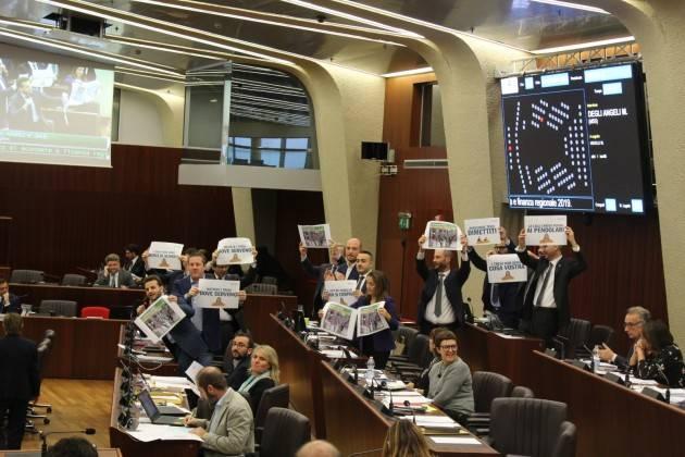 Il M5S Lombardo protesta in Cons.Reg. con cartelli 'I treni non sono merci di scambio' e chiede dimissioni l' Assessore Terzi