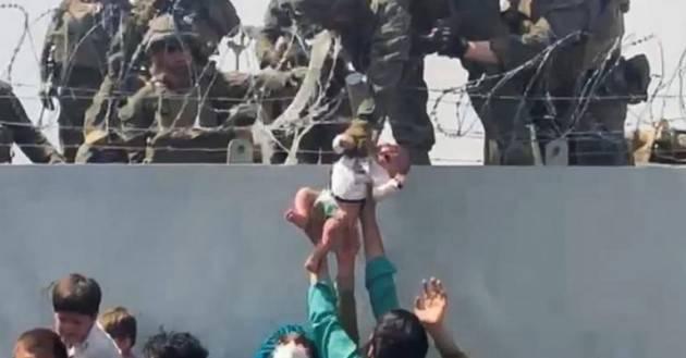 La foto marine che afferra un bambino passato da una donna afghana